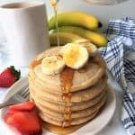 fluffy vegan pancakes with sliced bananas and strawberries
