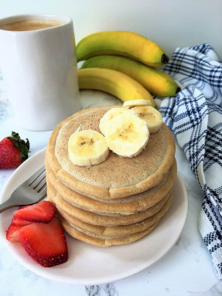 vegan pancakes plated with banana and strawberry slices