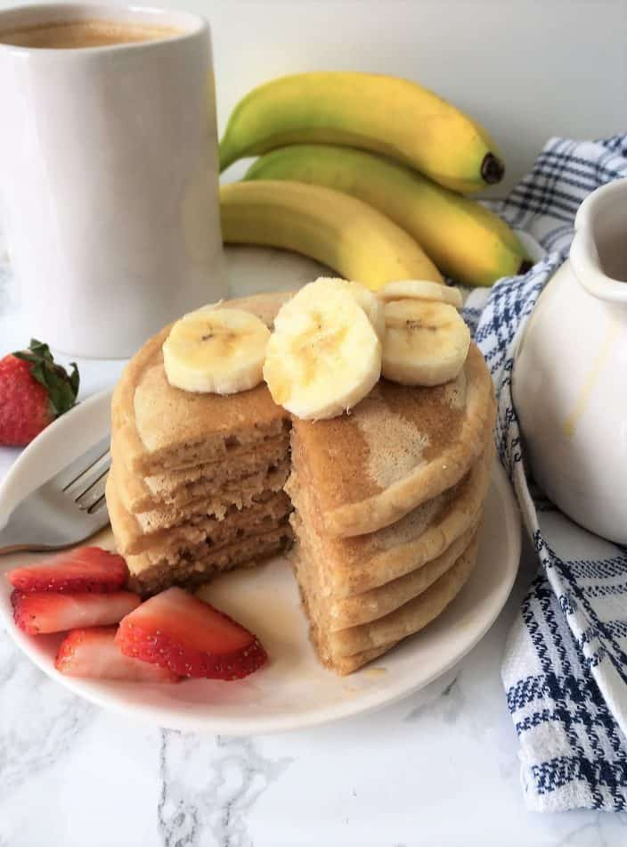 vegan pancakes stacked on plate with triangular slice through the stack