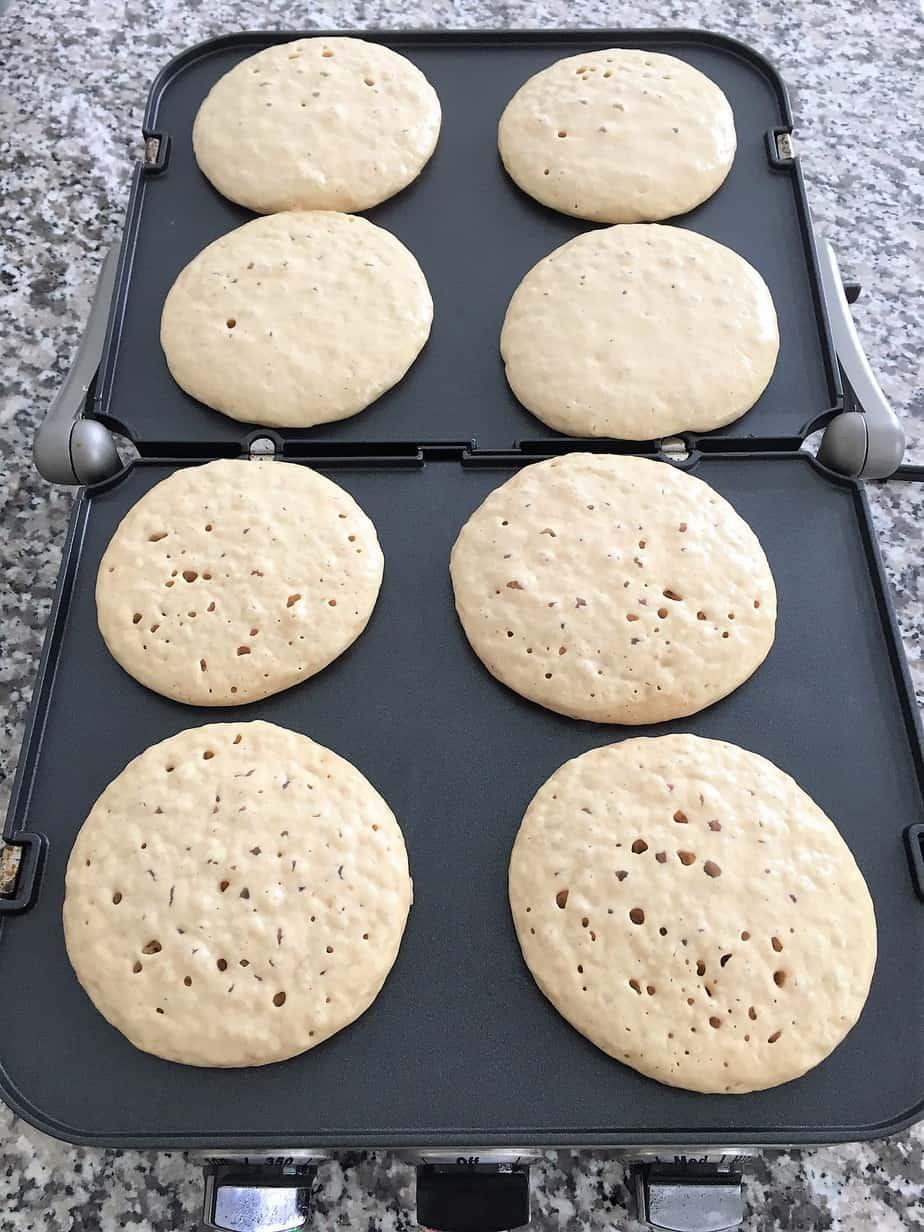 vegan pancakes cooking on griddle