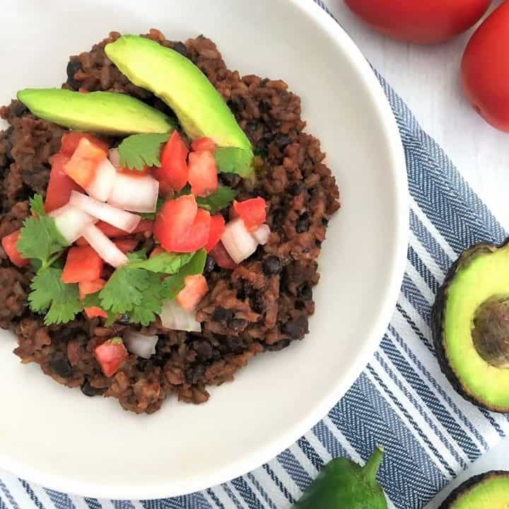Rice and beans in white plate with tomato, onion and avocado garnish.