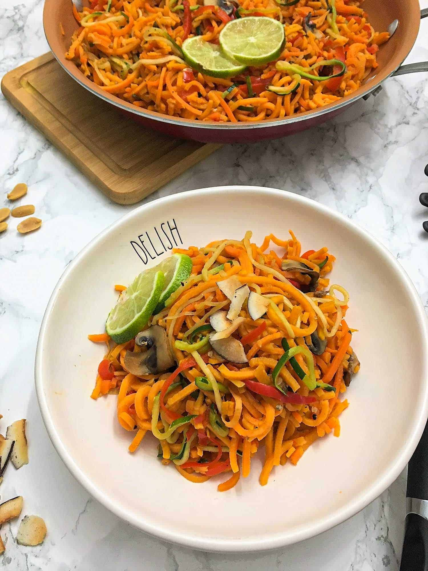 veggie noodles in plate with lime slices garnished over top