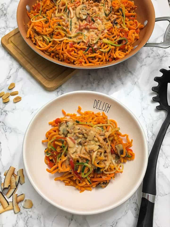 veggie noodles with coconut peanut sauce over top in plate
