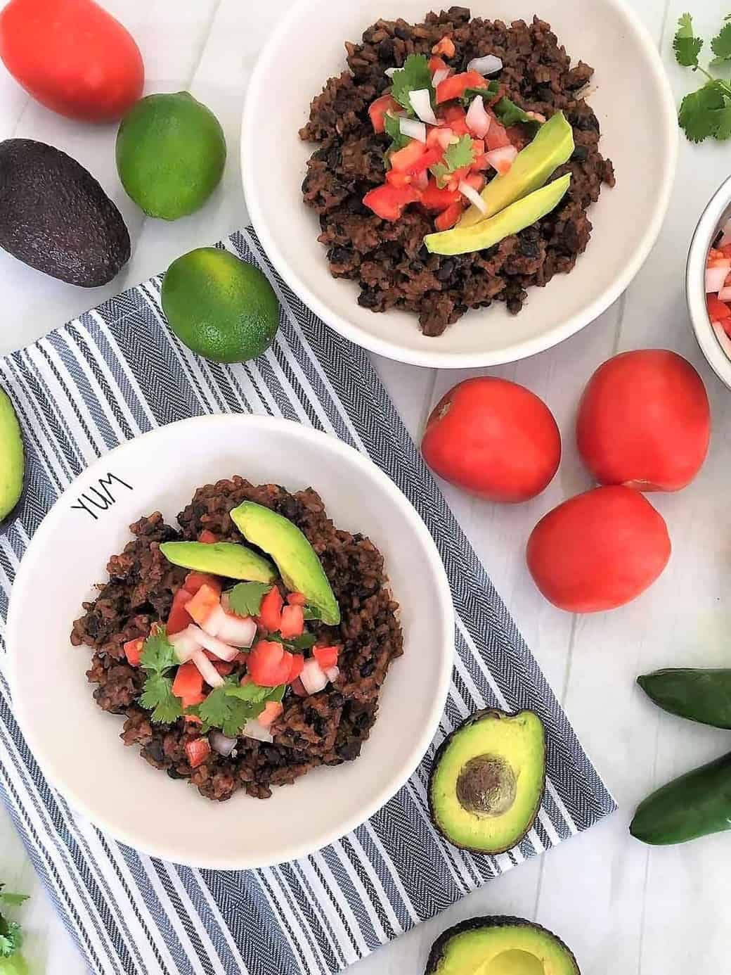 Two white plates of rice and beans with avocado slices, diced tomato and cilantro on top.