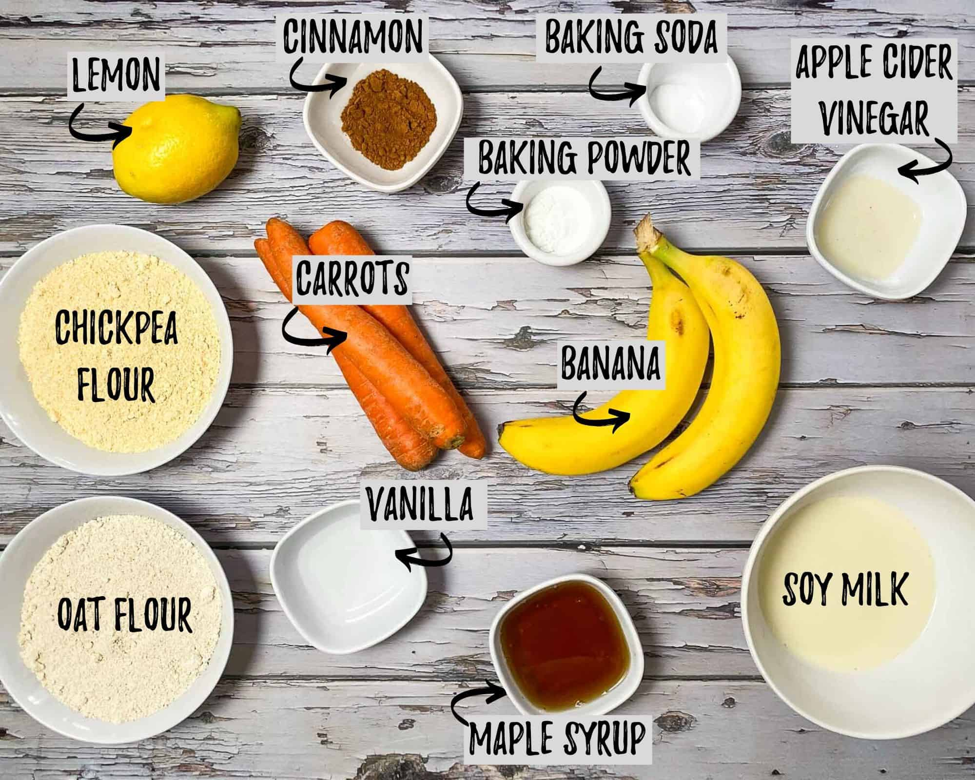 bananas, bowl of flour, carrots, syrup, lemon and spices in bowls on grey deck