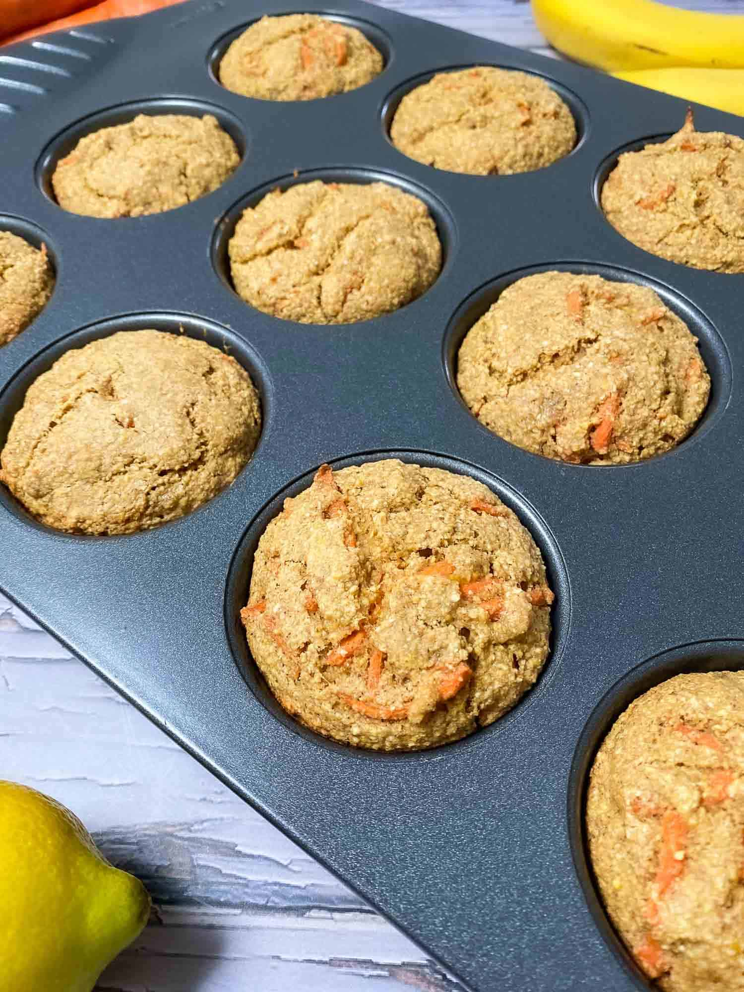 muffin pan with baked banana carrot muffins inside