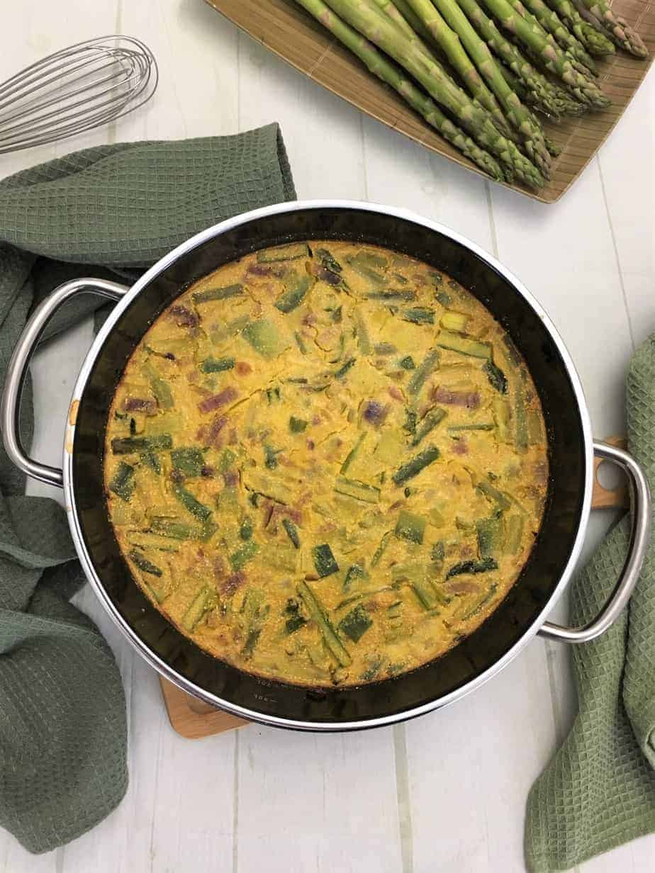asparagus frittata cooked in pan on cutting board