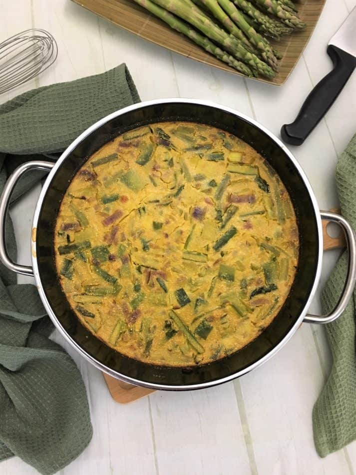 vegan asparagus frittata in pan on cutting board