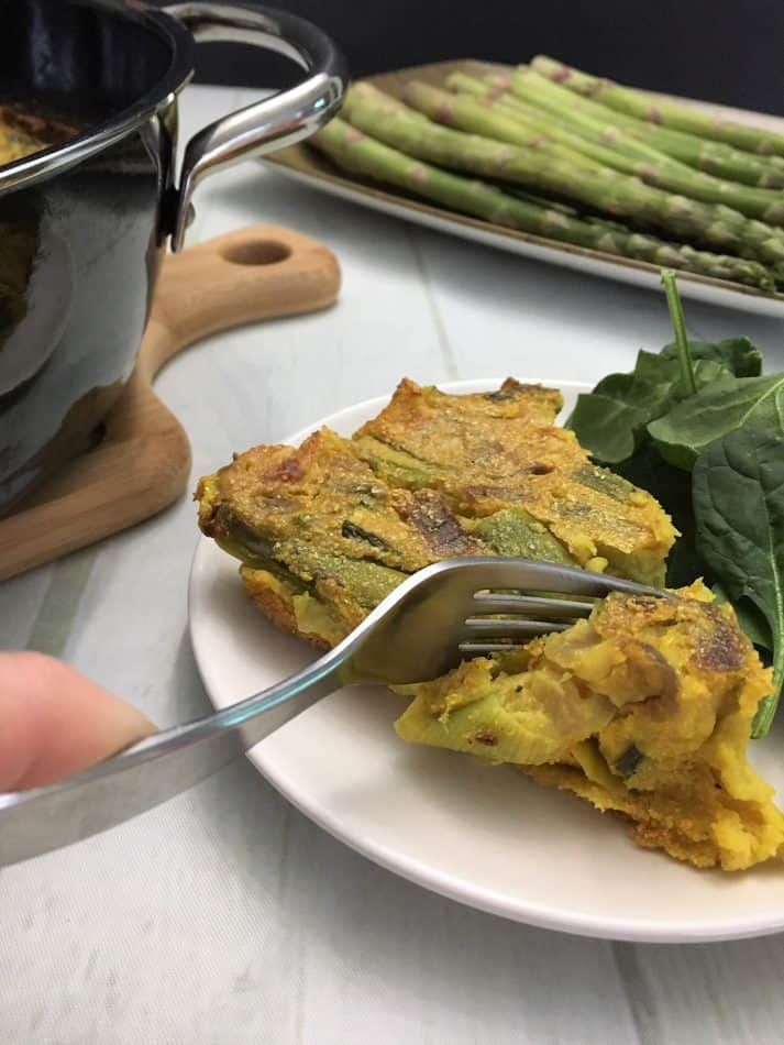 asparagus frittata sliced on plate with fork cutting in to take a bite