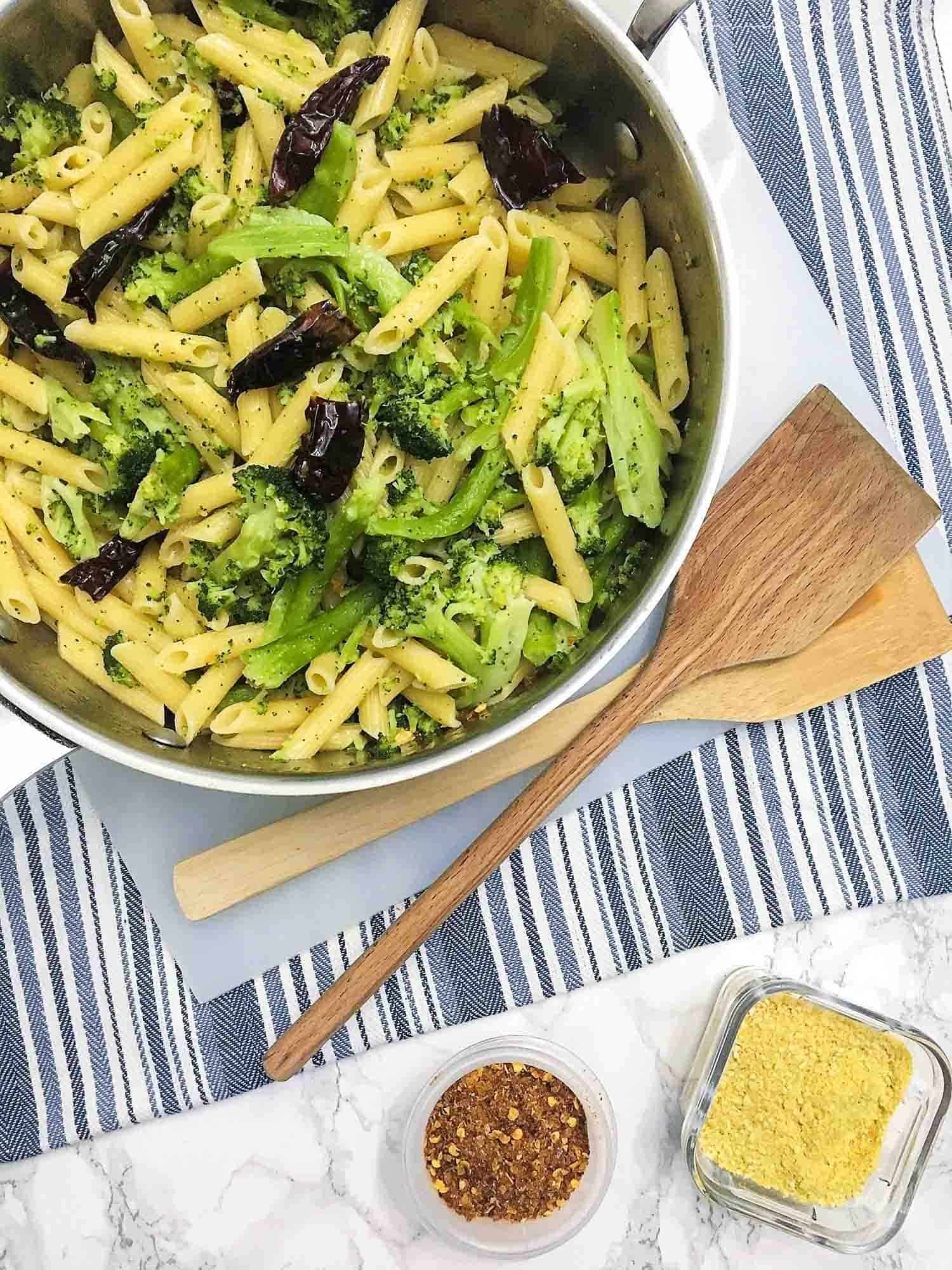 Penne pasta with broccoli and dehydrated chili peppers in stainless steel pan.