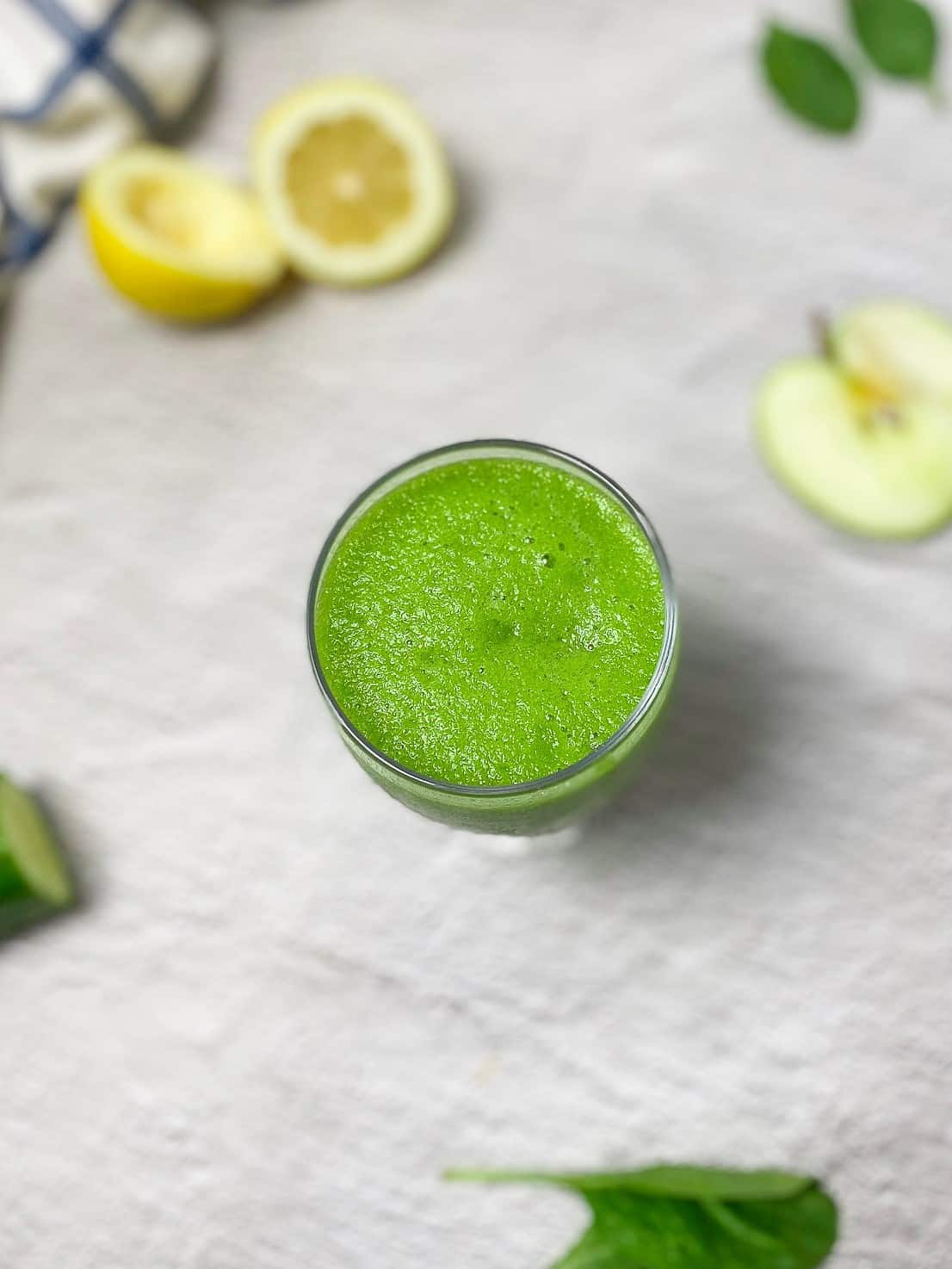 overhead view of sour apple smoothie in clear glass