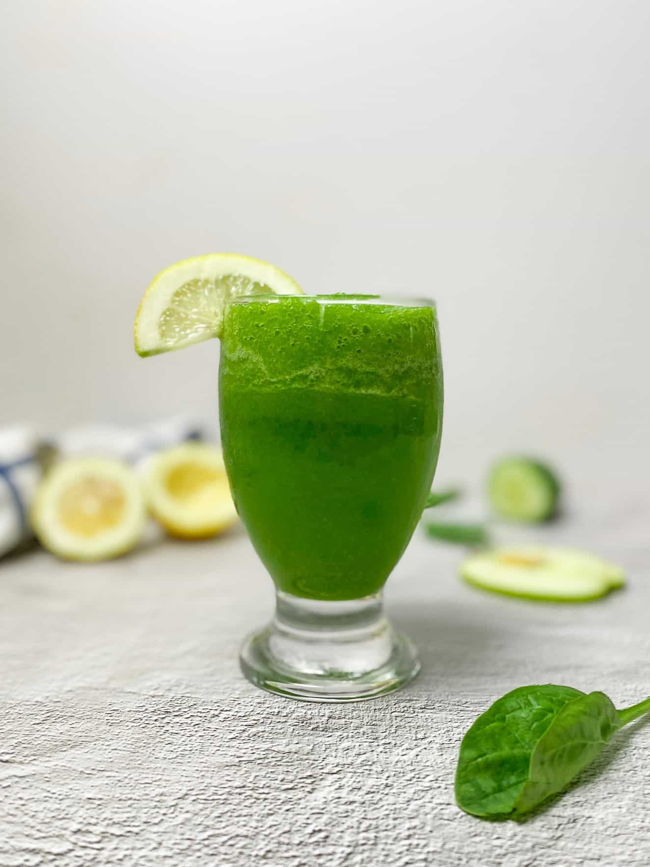 green smoothie in glass with lemon slice garnish