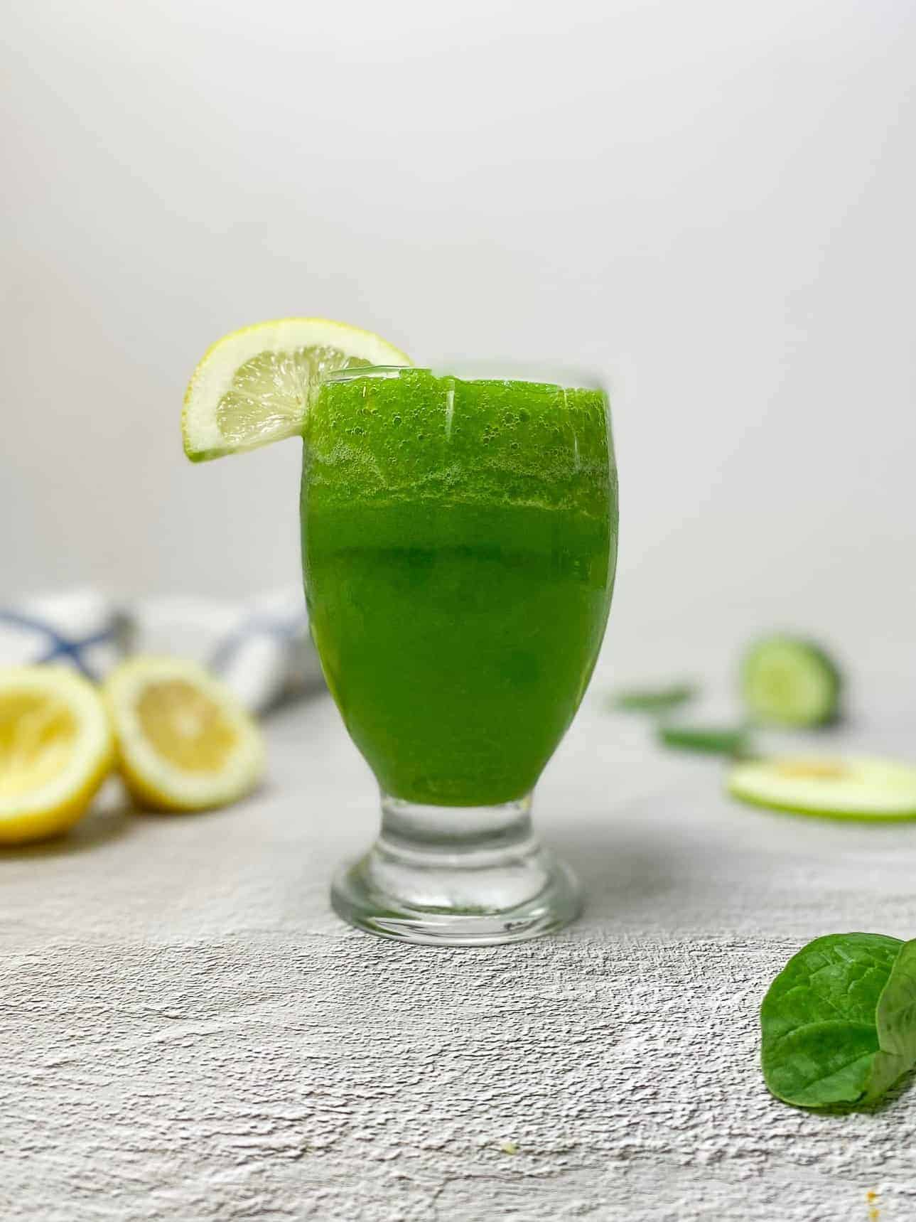 glass of sour apple smoothie with lemon wedge garnish