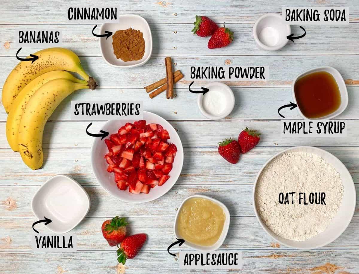 ingredients to make banana strawberry bread: bananas, strawberries, flour, applesauce, cinnamon, maple syrup, baking powder and soda