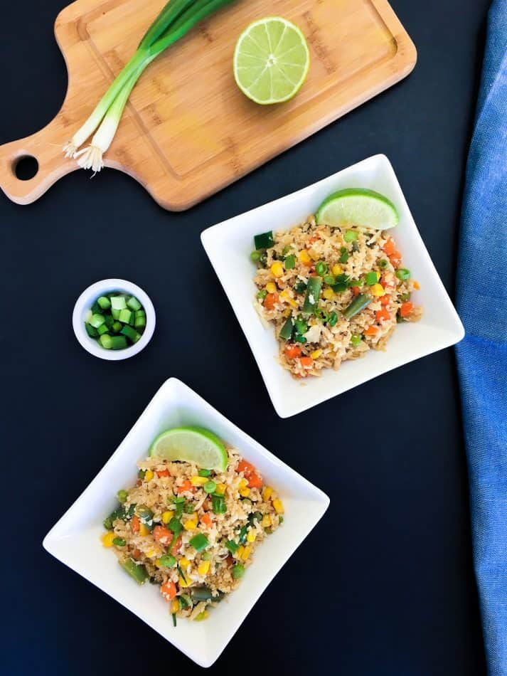 Cauliflower fried rice in two bowls with green onion garnish