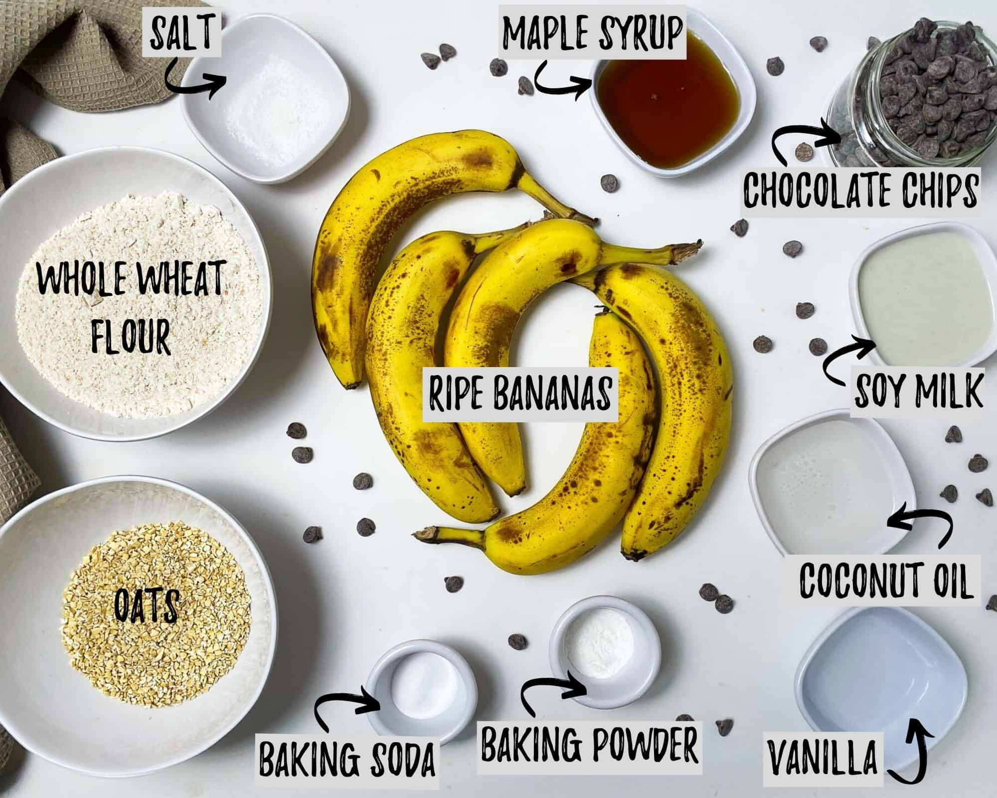 bananas, bowl of flour, bowl of oats, baking powder, baking soda, maple syrup, vanilla, milk, oil, salt