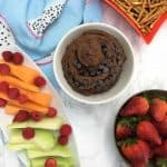 chocolate hummus in bowl with tray of melon, raspberries, strawberries and pretzels for dipping