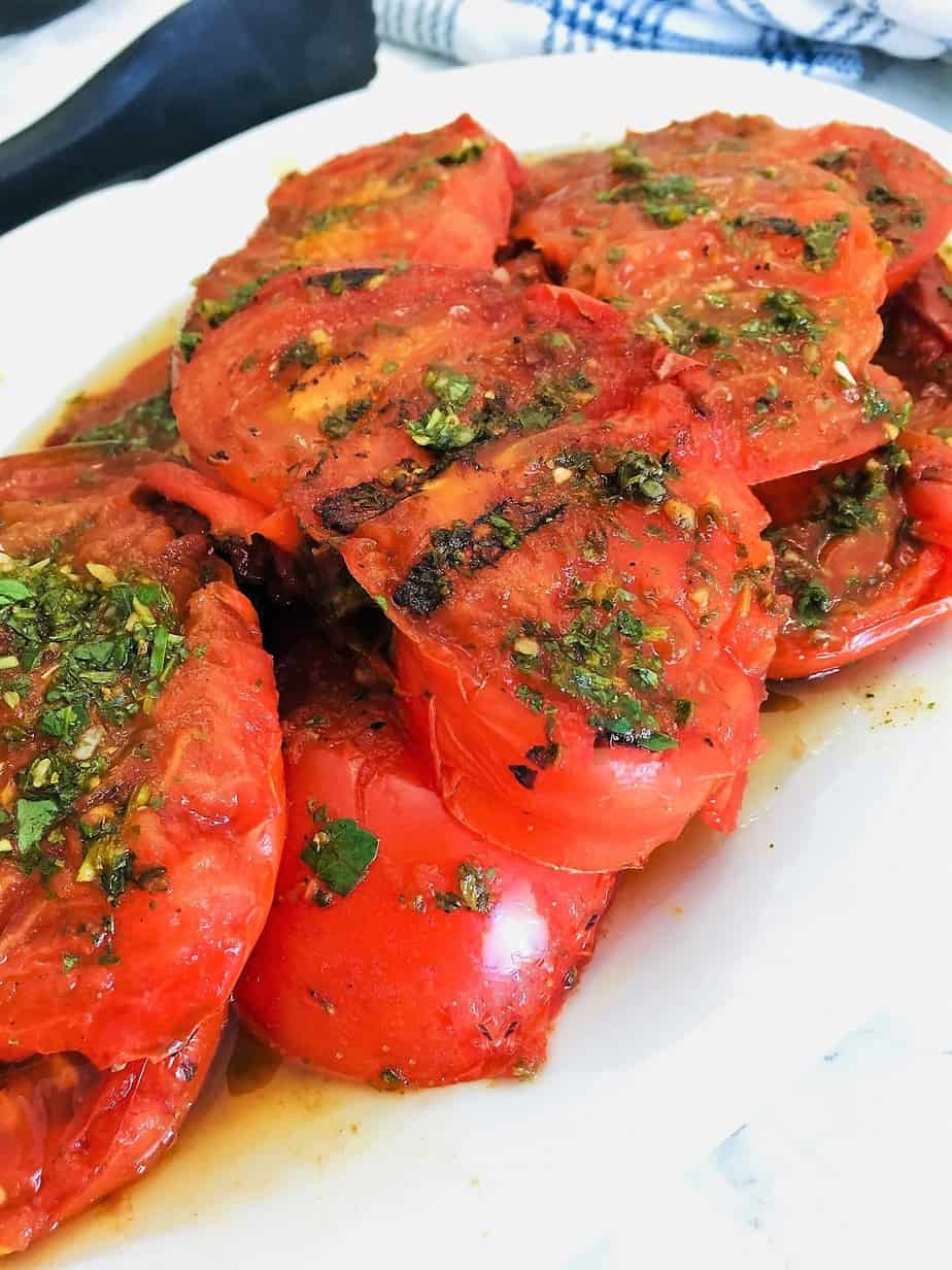 White platter with sliced grilled tomatoes on it and chimichurri on top.