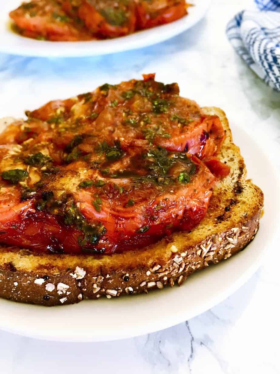 Slice of toast with grilled tomato on top in white plate.