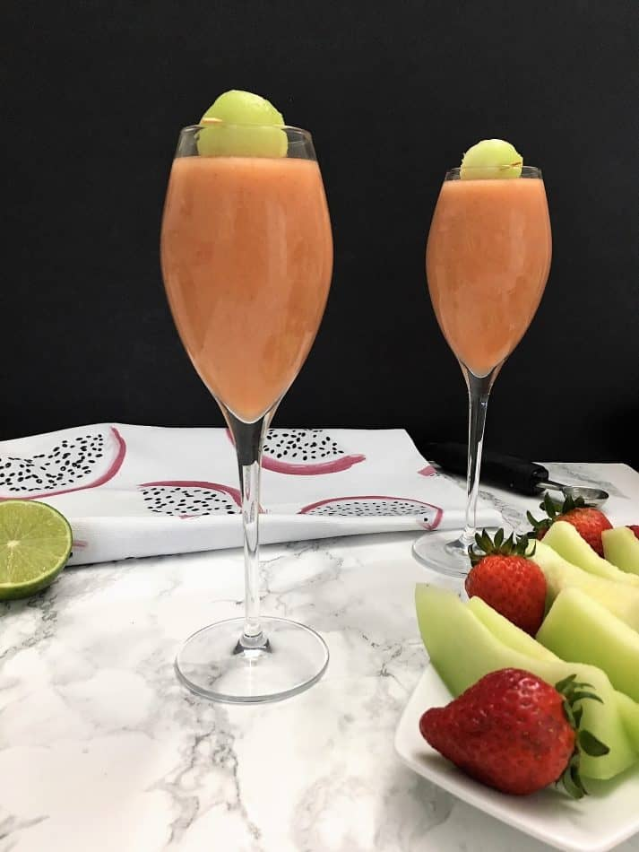 smoothie in two flutes with tray of strawberries and honeydew in front