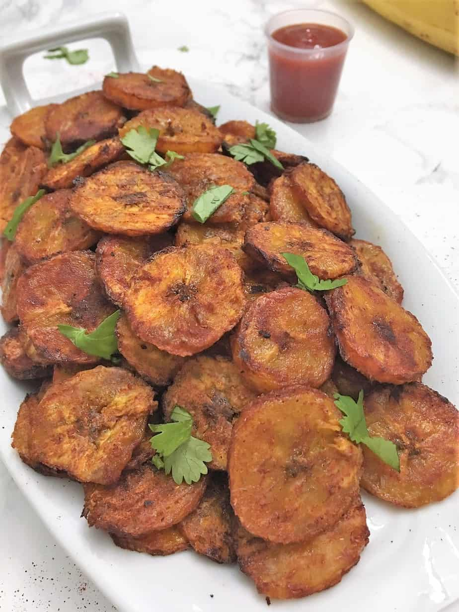 Plantain chips on white serving dish.