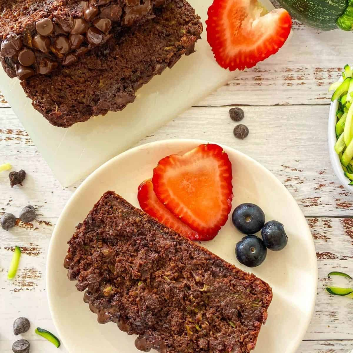 Slice of chocolate zucchini bread on white plate with strawberries and blueberries beside it.