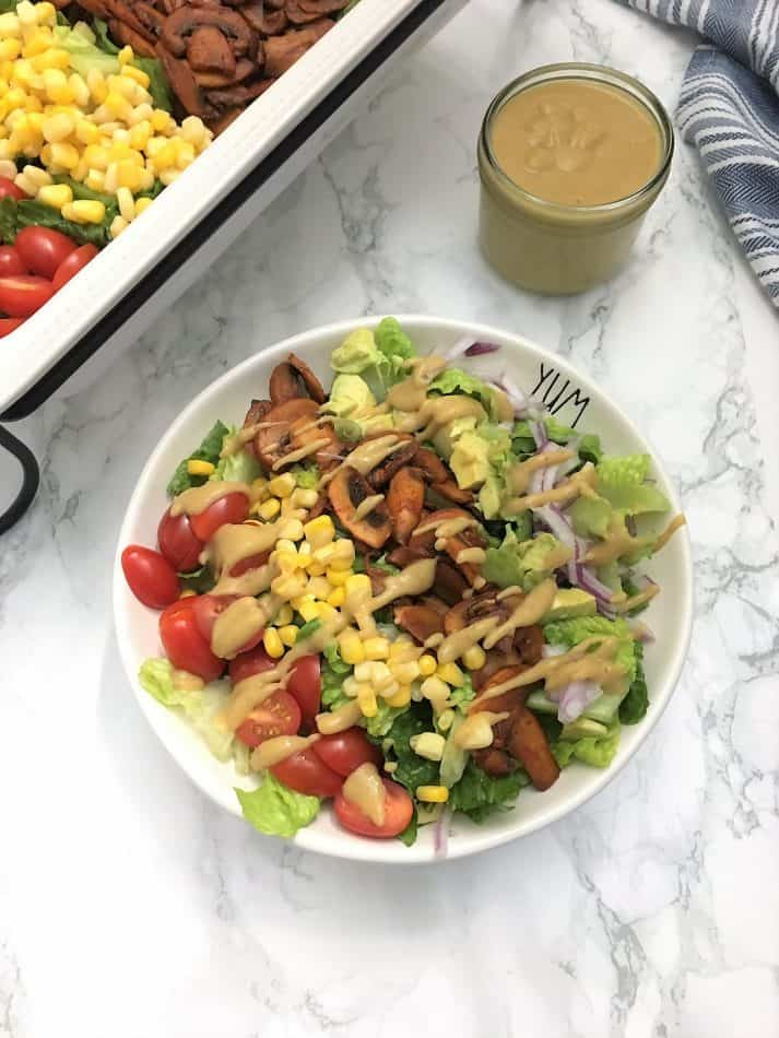 salad topped with corn, tomato, smoky mushrooms, avocado, red onion and vegan cheesy dressing
