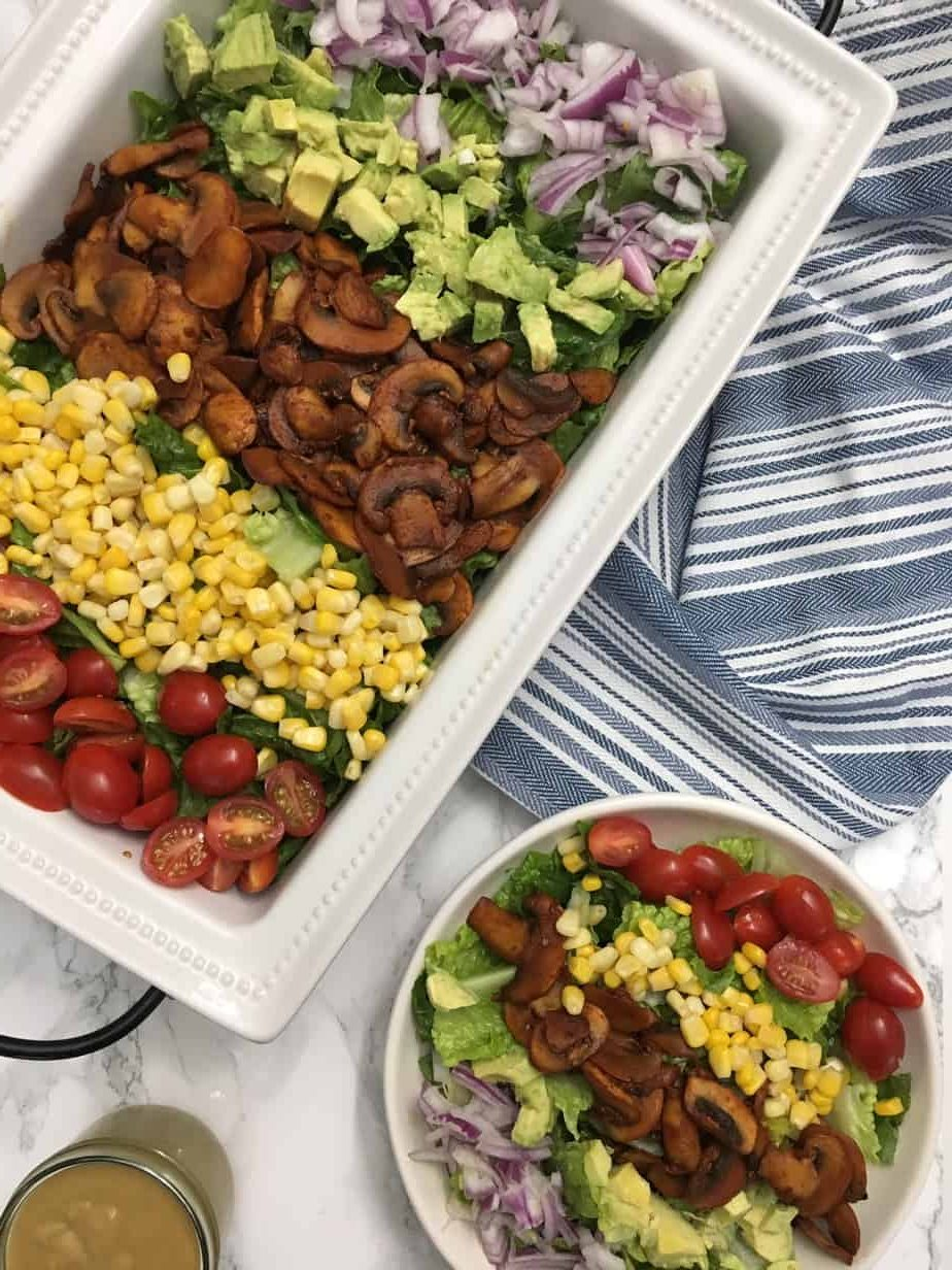 salad topped with tomato, corn, mushrooms, avocado, red onion