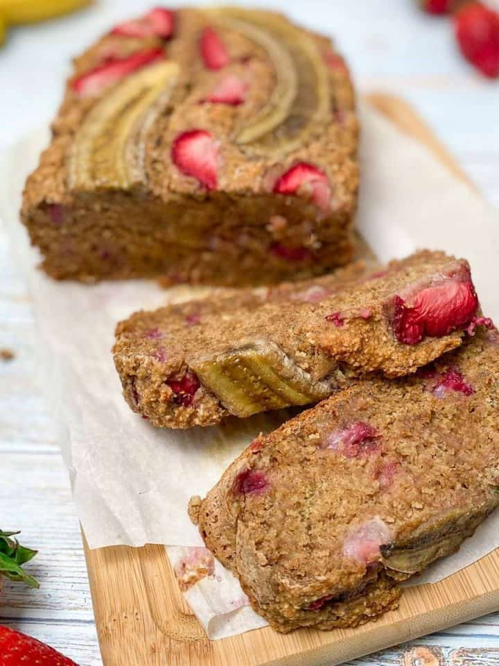 strawberry banana bread on cutting board with two slices cut