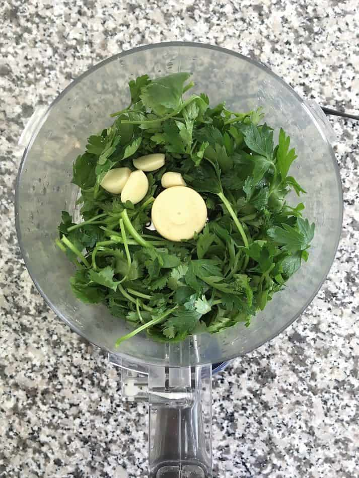 cilantro, parsley, garlic in food processor before pulsing