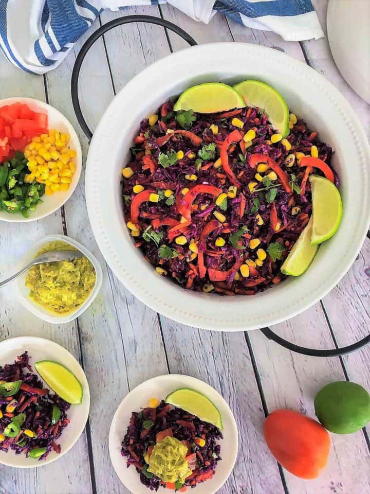 Mexican salad served in three plates topped with lime and guacamole