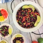 Mexican salad in serving dish garnished with lime wedges