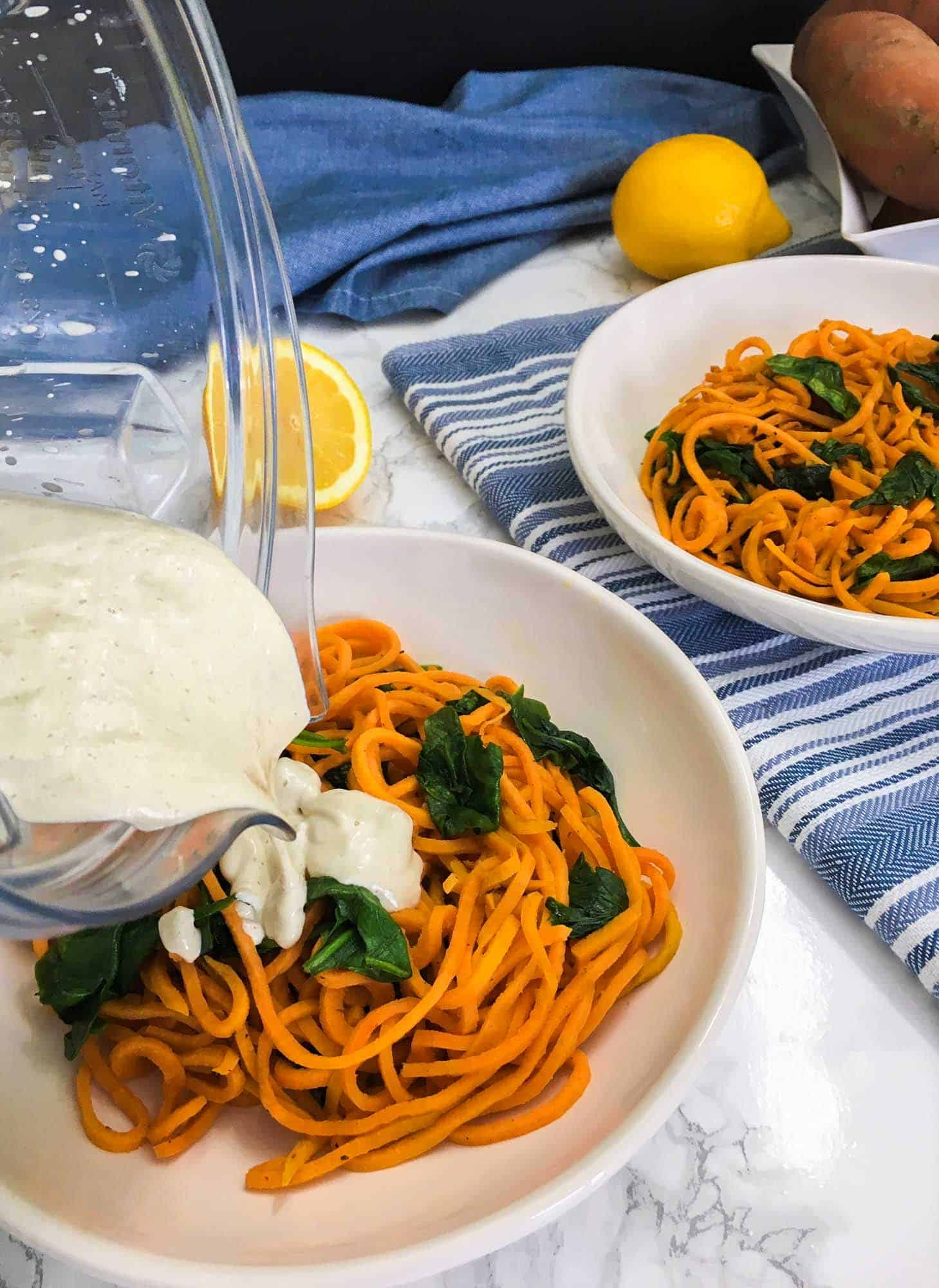 pouring vegan alfredo sauce from blender over plate of sweet potato noodles