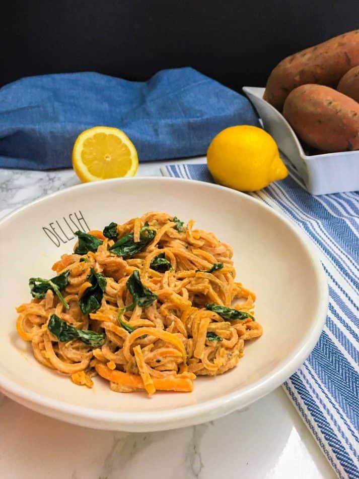 vegan alfredo sauce mixed into bowl of sweet potato noodles