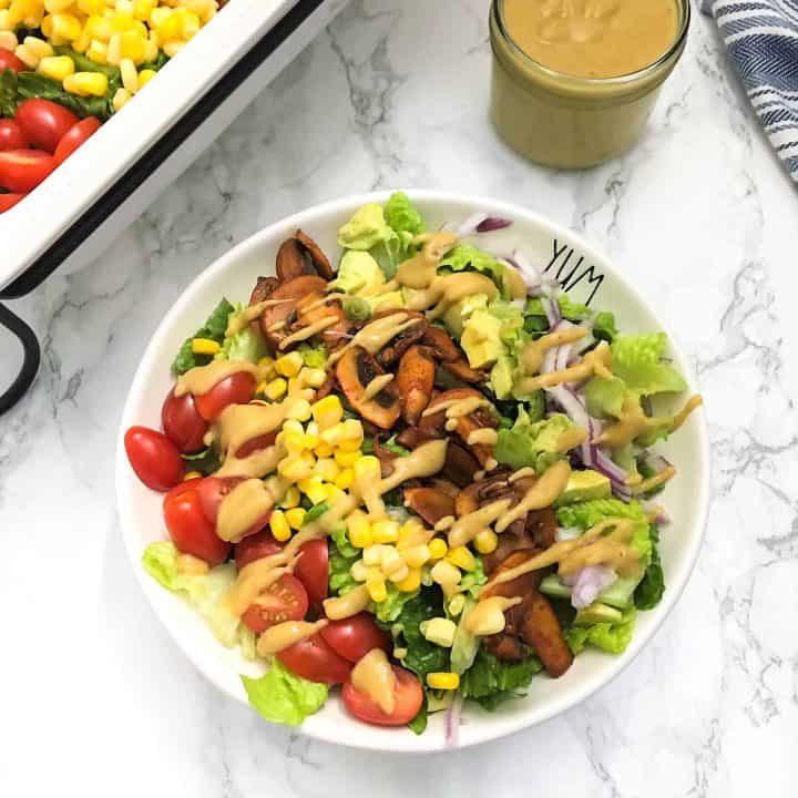 Plate of salad with rows of onion, mushrooms, corn, tomato and avocado on top.