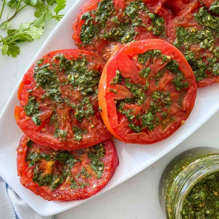White platter filled with sliced grilled tomatoes with chimichurri on top.