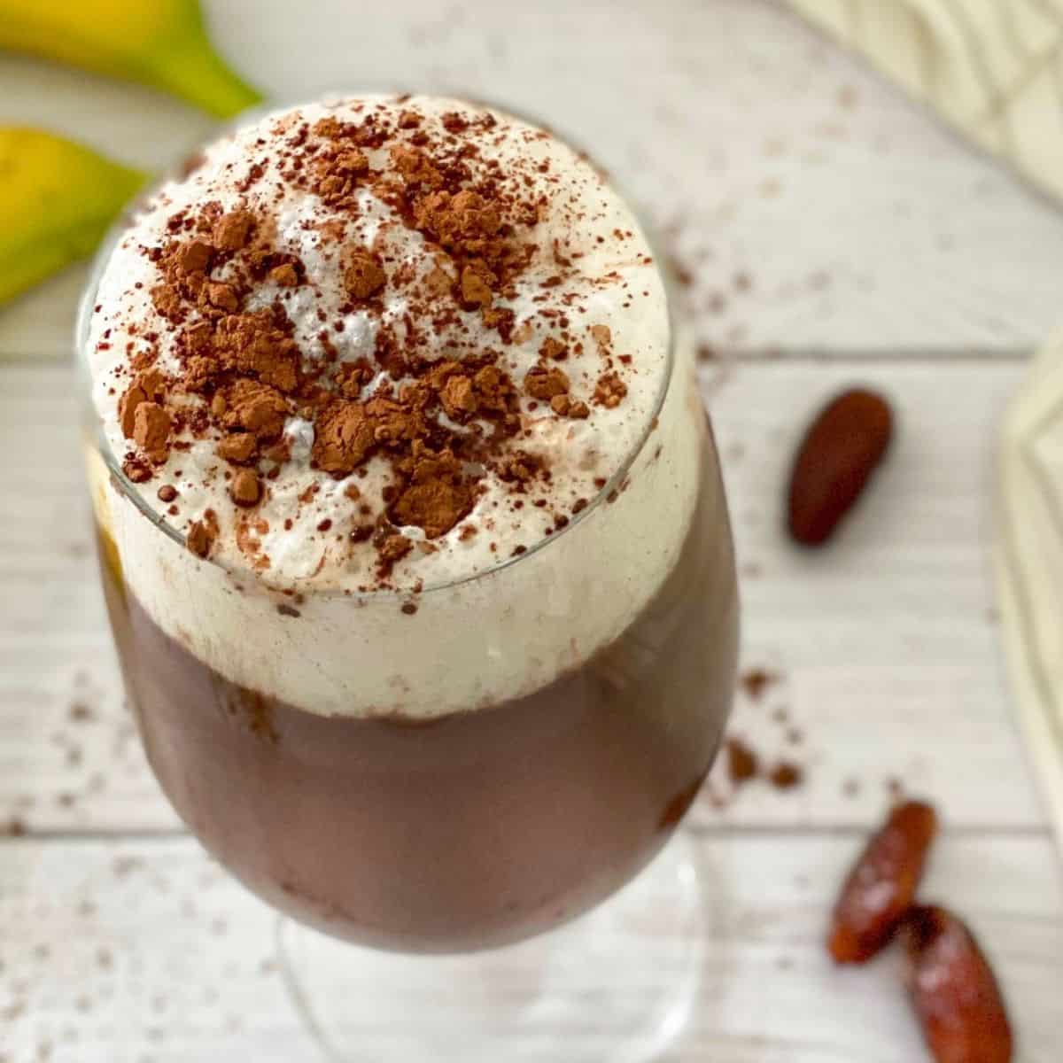 Overhead view of glass with iced mocha with dates and bananas around it.