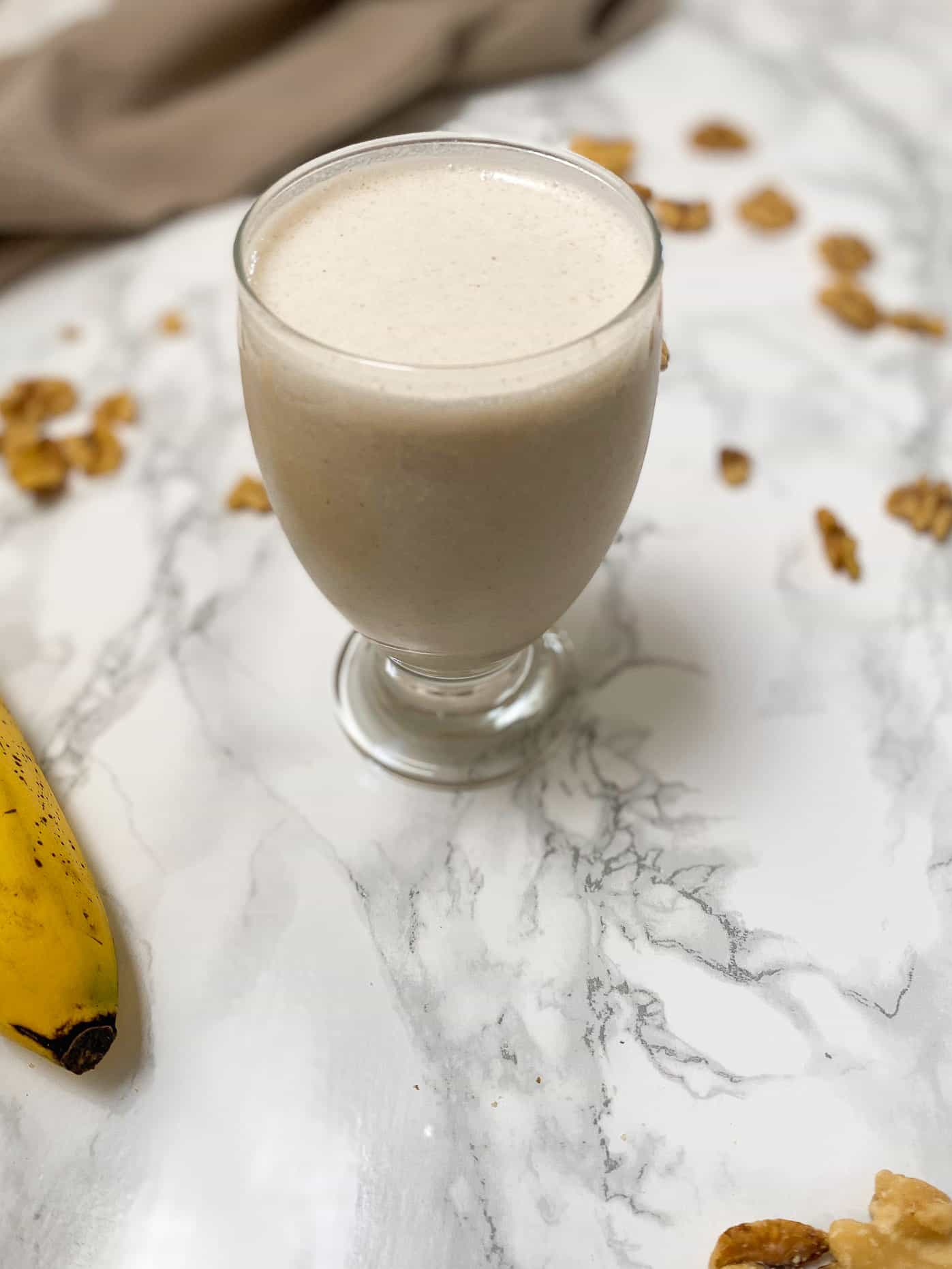 banana walnut smoothie in glass cup with walnuts and banana scattered around