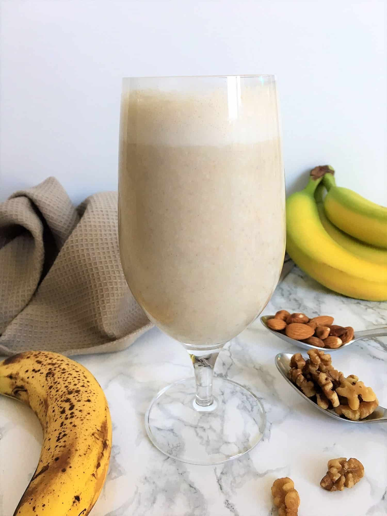 glass filled with banana smoothie with nuts and bananas on counter beside glass