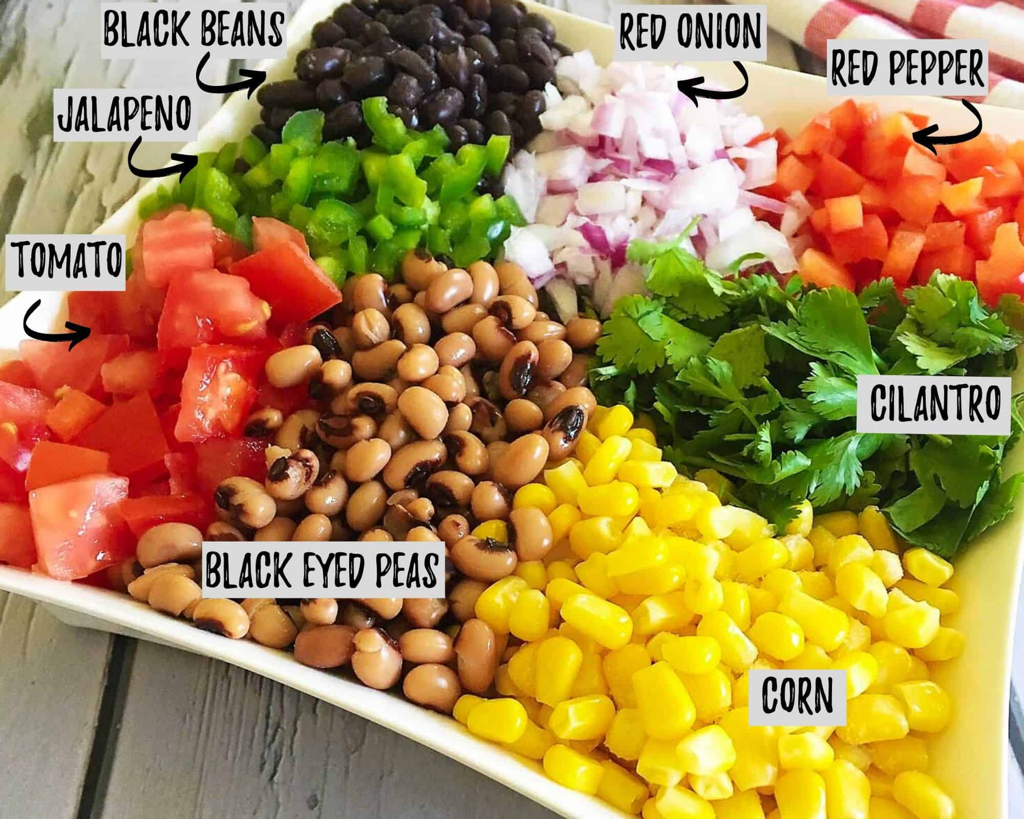 ingredients to make cowboy caviar: beans, tomato, corn, cilantro, red pepper, jalapeno, red onion