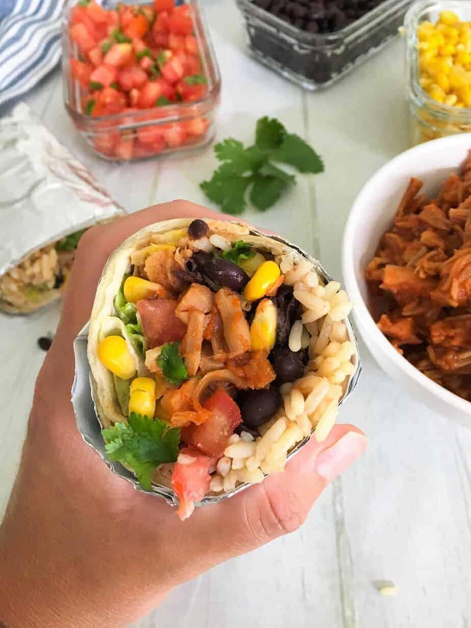hand holding up burrito