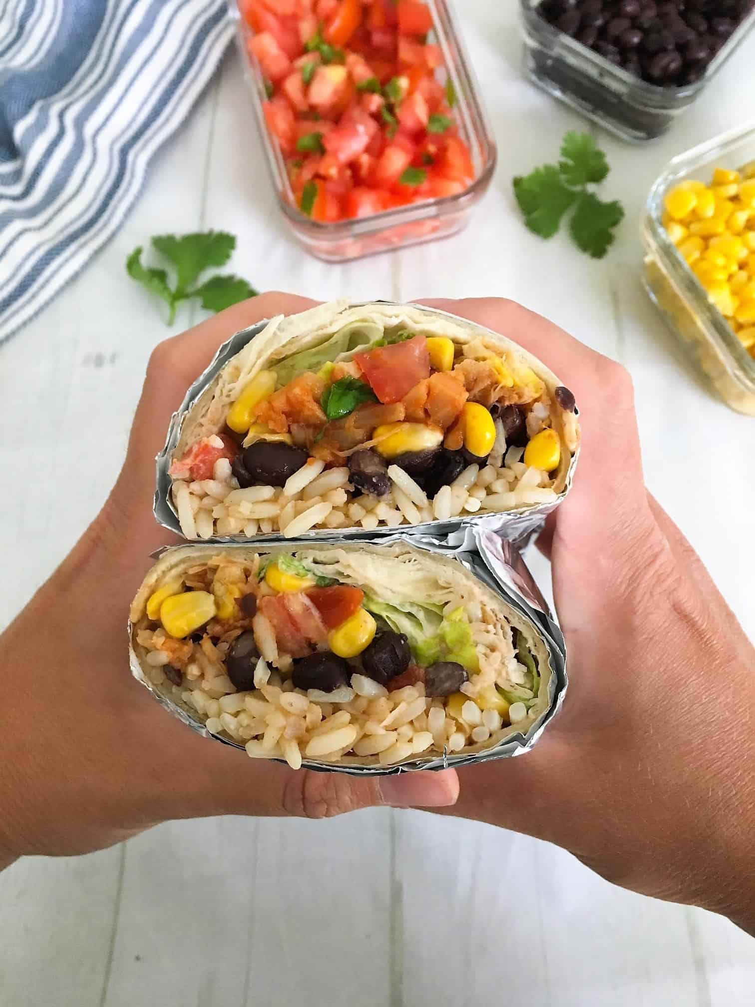 burritos stuffed with jackfruit, beans, corn, rice and lettuce being held up in hands