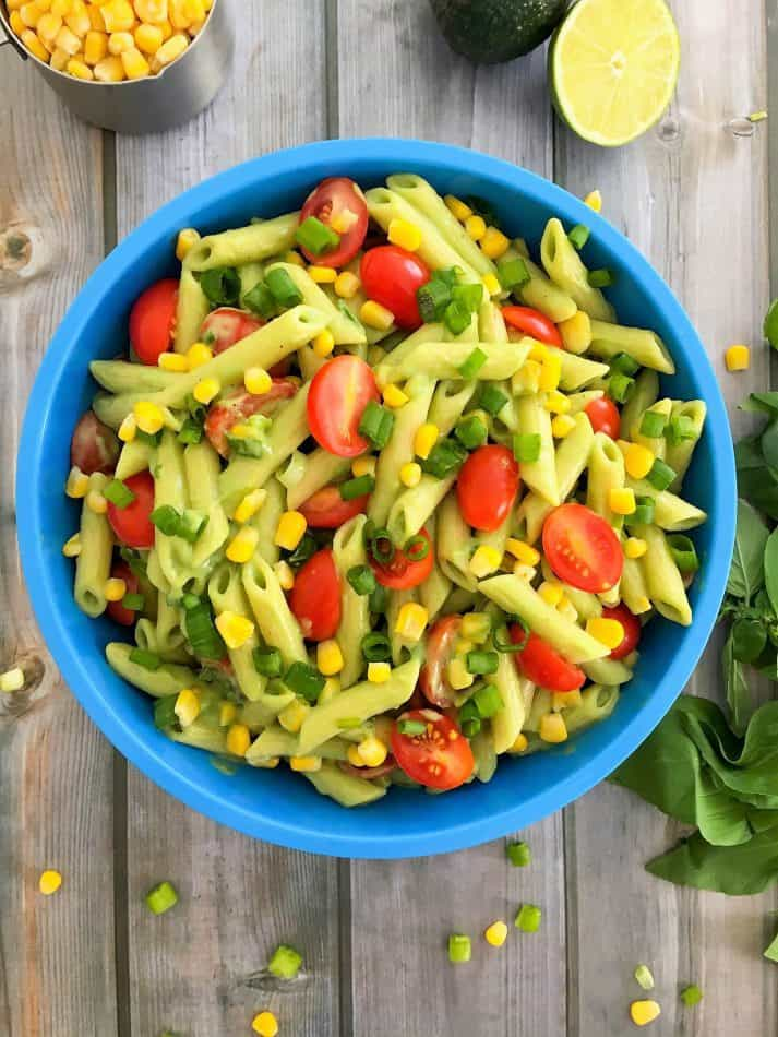 pasta salad in blue bowl with cherry tomatoes, corn, green onion