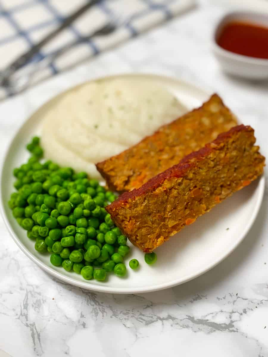 two slices of vegan loaf with mashed cauliflower and sweet peas on round plate