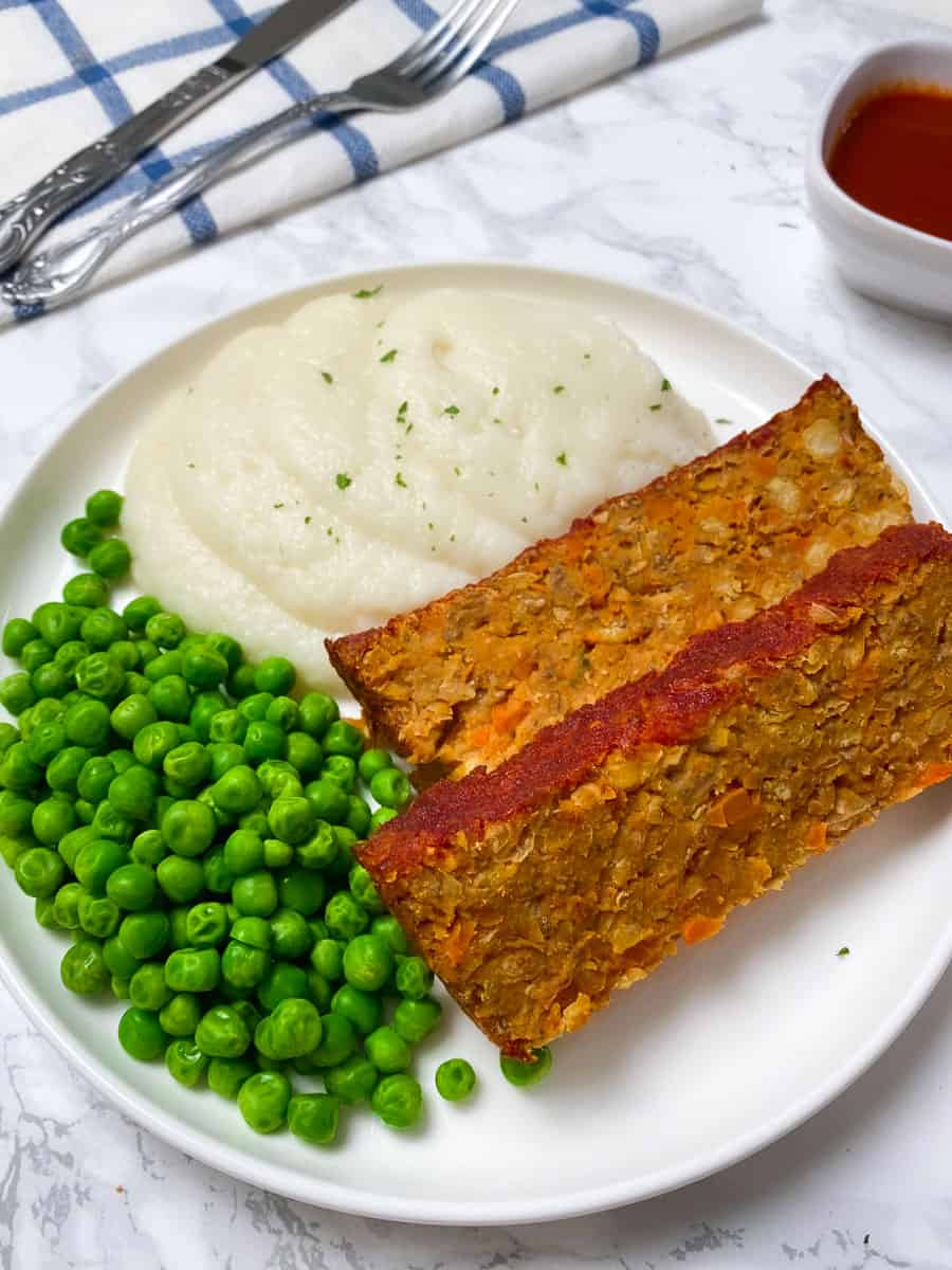 chickpea loaf on plate with side of mashed cauliflower and green peas