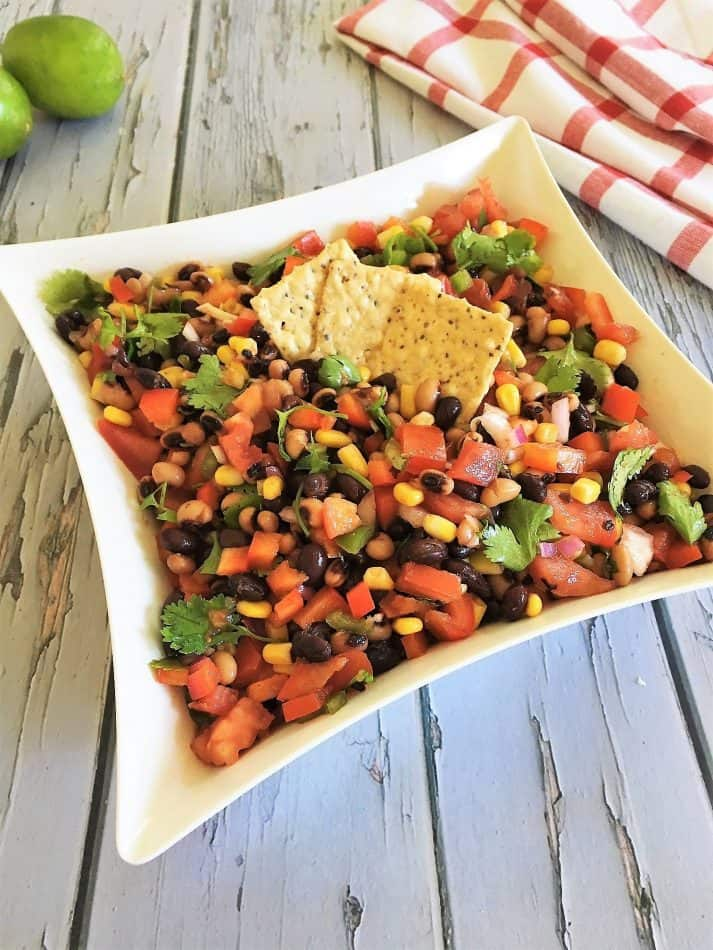 bean salad in white square bowl with crackers on top