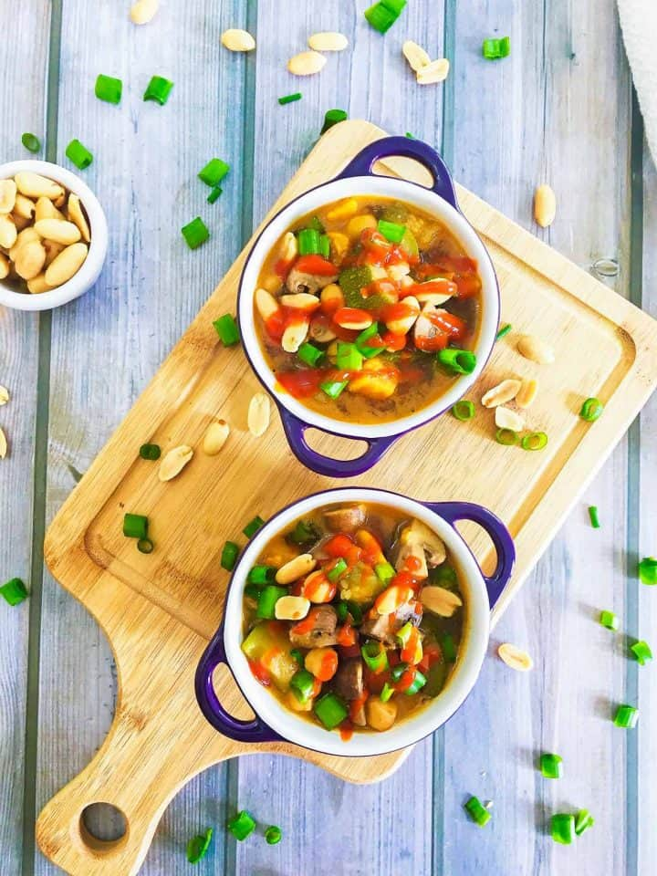 chickpea soup in two bowls with green onion and peanut garnish