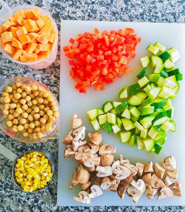 sweet potatoes, chickpeas, corn, mushrooms, zucchini, red pepper on cutting board