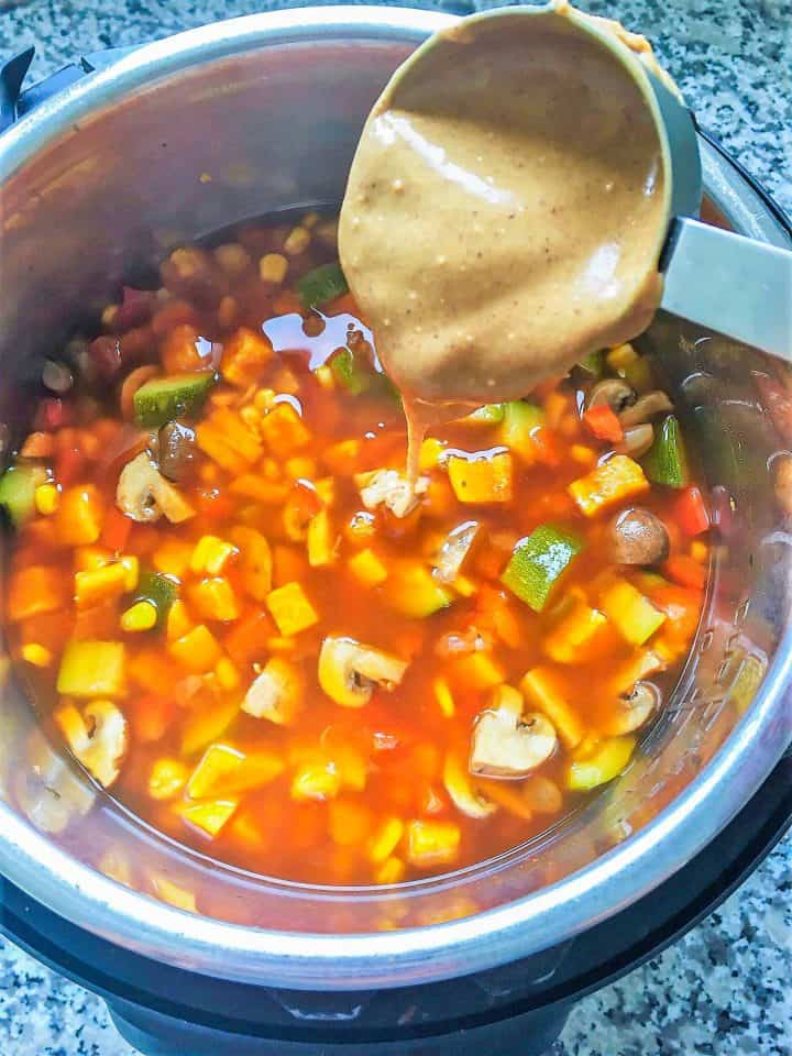 peanut butter pouring over chunky soup in instant pot