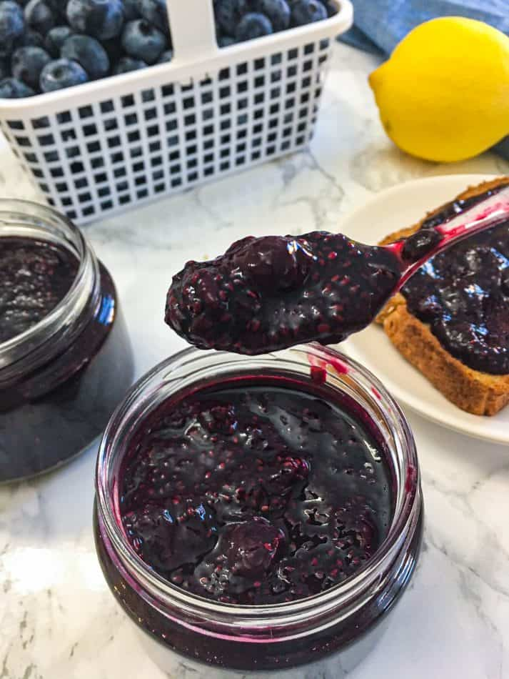 spoon of blueberry jam being held over jar
